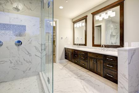 明るく風通しの良いマスターの浴室は、白現代二重虚栄心と豊富なブラウンのキャビネットと大理石のシャワーを備えています。米国北西部 写真素材