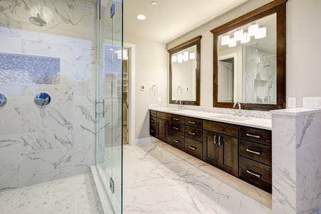 La salle de bains principale lumineuse et aérée comporte la double meuble-lavabo moderne blanche avec de riches armoires brunes et une douche à l'italienne en marbre. Northwest, États-Unis Banque d'images - 90010879