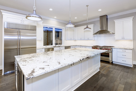Grande, espaçoso design de cozinha com armários de cozinha brancos, ilha de cozinha branca com lotes de armazenamento, bancadas em granito branco, azulejos de metrô e utensílios de aço inoxidável. Noroeste, EUA. Noroeste, EUA