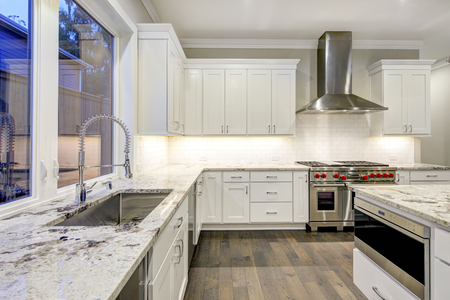 Large, spacious kitchen design with white kitchen cabinets, white kitchen island with lots of storage, white Granite countertops, subway tiles and stainless steel appliances. Northwest, USA . Northwest, USA Stock Photo