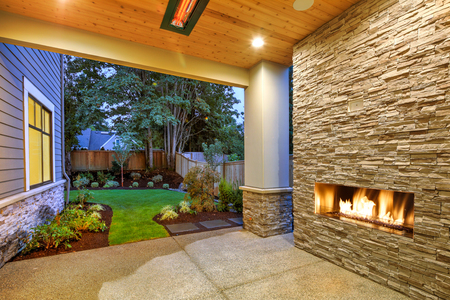 Outside Patio features natural wood plank ceiling, concrete floor and oversized stone fireplace overlooking a beautiful luxury yard.  Northwest, USA Stock Photo