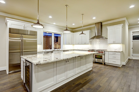 Large, spacious kitchen design with white kitchen cabinets, white kitchen island with lots of storage, white Granite countertops, subway tiles and stainless steel appliances. Northwest, USA  Archivio Fotografico