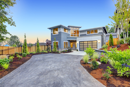 Excellent curb appeal of a Modern craftsman style home accented by landscaping, garage with glass door and long asphalt driveway. Northwest, USA Stockfoto