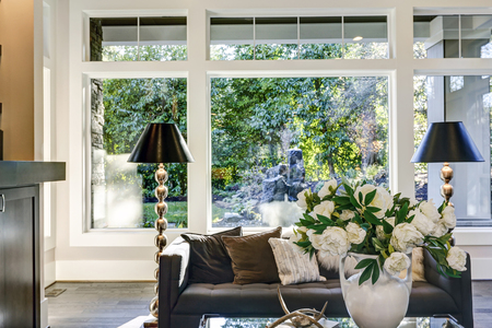 Chic living room nook showcases grey tufted sofa flanked by a pair of black floor lamps next to window wall overlooking  lush outdoors. Northwest, USA