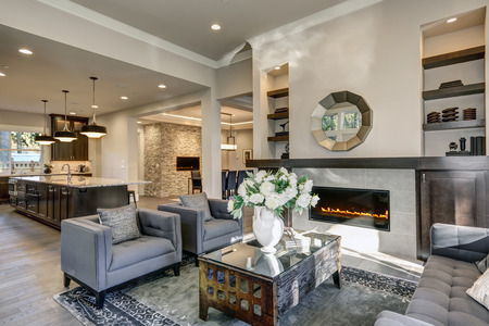 Chic living room filled with built-in cabinets flanking round mirror atop grey tile fireplace, tufted sofa facing two armchairs and window wall overlooking  lush outdoors. Northwest, USA
