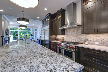 Modern kitchen with brown kitchen cabinets, oversized kitchen island, granite countertops, stainless steel hood over six burner Range and beige backsplash. Northwest, USA