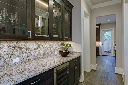 Brown wet bar boasts glass front cabinets paired with gray and white granite countertops . Northwest, USA