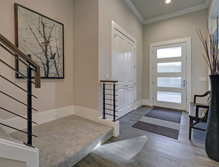 Bright entryway with creamy walls highlighting modern glass door over gray hardwood floors. Includes white doors built-in closet, wood bench and staircase with horizontal railings. Northwest, USA  Standard-Bild