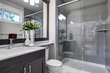 明るい新しいバスルームのインテリアは、灰色のタイルサラウンド、茶色の化粧台は白いカウンターでトッピングし、モザイクタイルバックスプラ