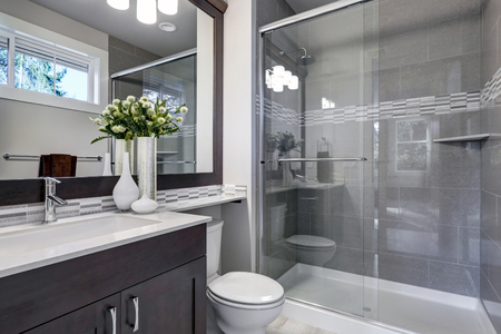 Bright new bathroom interior with glass walk in shower with grey tile surround, brown vanity cabinet topped with white counter and paired with mosaic tile backsplash. Northwest, USA  Stockfoto