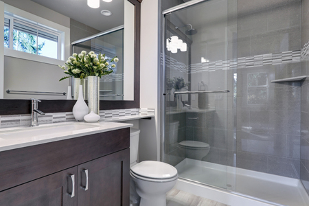 Bright new bathroom interior with glass walk in shower with grey tile surround, brown vanity cabinet topped with white counter and paired with mosaic tile backsplash. Northwest, USA  Archivio Fotografico