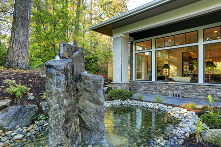 Luxurious new construction home exterior with perfect landscape design: nice garden pond with stone fountains. Northwest, USA