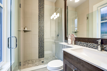 Bright new bathroom interior with glass walk in shower, brown vanity cabinet topped with white counter and paired with mosaic tile backsplash. Northwest, USA