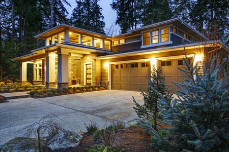 Luxurious new construction home exterior at sunset. View of two garage spaces with concrete driveway and illuminated porch with columns. Northwest, USA