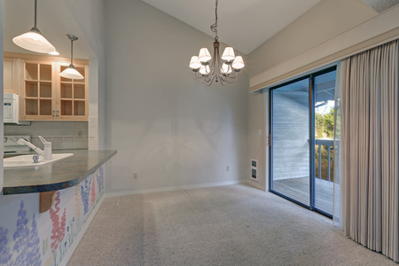 Empty dining space with vaulted ceiling and grey walls paint color. Glass sliding doors lead out to back deck. Northwest, USA