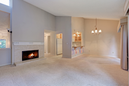 Empty living space with vaulted ceiling, grey walls paint color and carpet floor.  Cozy wood burning fireplace with beige tile surround. Northwest, USA Stock Photo