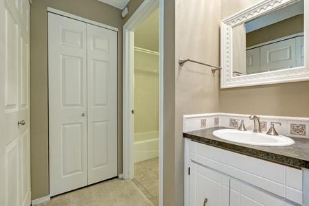 Beautiful bathroom with white single vanity, dark quartz countertop with undermount sink and Mosaic backsplash,  white folding closet doors. Northwest, USA