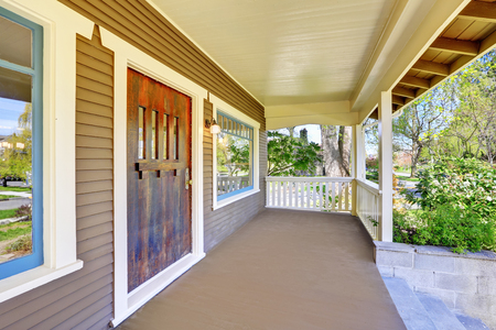 Stately completely renovated Craftsman home exterior: covered empty entrance porch accented with white trim. This historic home was designed and constructed by Henry Schneider. Stock Photo
