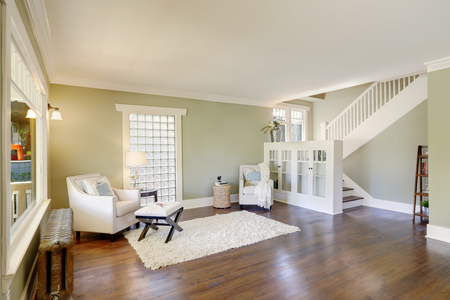 Lovely Green Living Room With Built In Bookshelves, Crown Molding And A  Staircase.