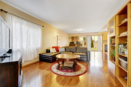 Open floor living room with warm yellow walls, wood laminate flooring, furnished with grey leather sectional, built in bookcase with open shelves and round coffee table. Northwest, USA