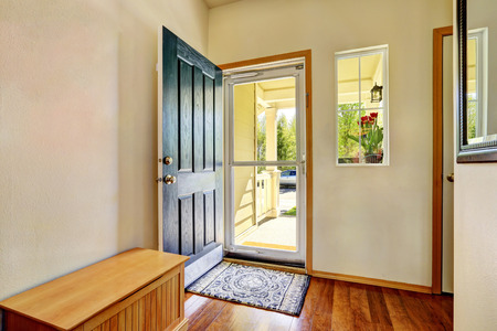 Small foyer with green open front door, laminate floor and wooden bench. Northwest, USA