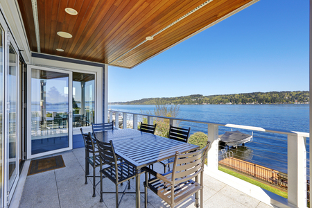 Large covered deck with comfortable outdoor dining space boasts planked ceiling with built-in lighting and shows stunning view of Lake Washington. Northwest, USA