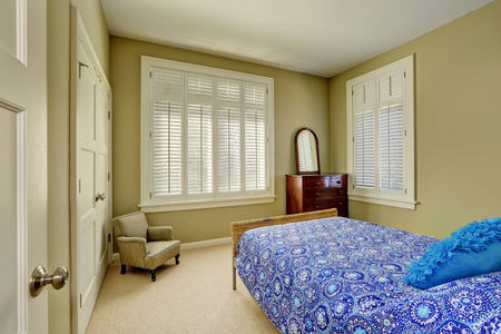 Green olive bedroom interior with blue bed, wood cabinet with drawers,  windows dressed in plantation shutters and walk-in closet. Northwest, USA