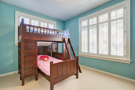 Green and blue kids room with a brown bunk bed accented with drawers and a built-in ladder. Northwest, USA Stock Photo