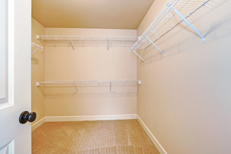 Empty walk in closet with shelves and carpet floor. Northwest, USA Stock Photo