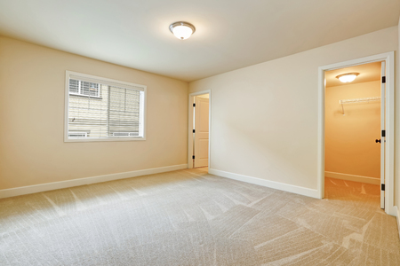 Light empty bedroom interior with soft sand beige walls paint color, walk in closet and own bathroom. Northwest, USA