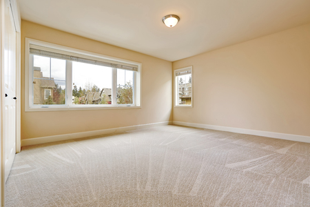 Light empty bedroom interior with soft sand beige walls paint color, walk in closet and wall to wall carpet. Northwest, USA Stock Photo