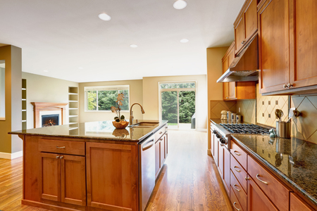 Bright Inviting kitchen boasts an oversized kitchen island topped with granite counter and opens to a brown empty great room with built in shelves. Northwest, USA Stock Photo