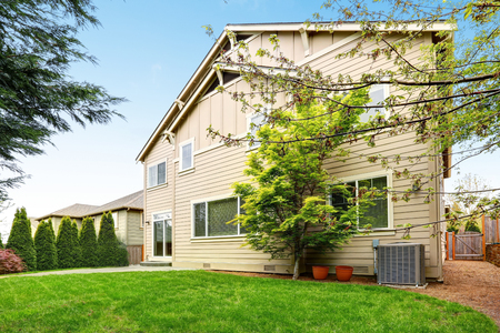 Lovely two story family home exterior with beige wood siding and well kept back yard. Northwest, USA