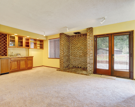 Empty family room interior with soft yellow walls, ready niche for log burner with brown brick surround and a wet bar. Northwest, USA