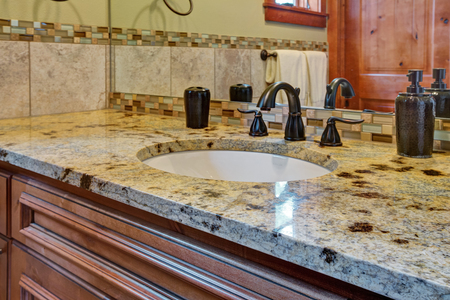 Master bathroom interior: bathroom vanity topped with granite countertop, green and brown glass tiles backsplash and black faucet. Northwest, USA