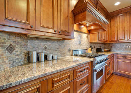 Gourmet kitchen boasts a curved kitchen hood over a subway tiled backsplash, granite countertops and a stainless steel stove flanked by brown wooden kitchen cabinets. Northwest, USA