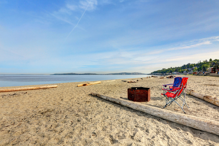 Alki Beach Park offers spectacular views of Puget Sound. Fire pit with  dry firewood on a sandy beach. Northwest, USA