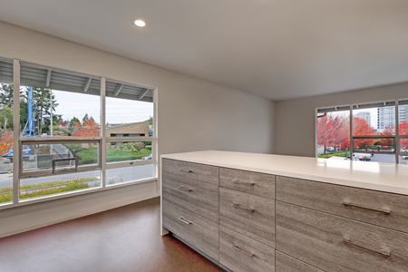 New modern apartment interior presents walls painted grey and large windows with nice view, also grey kitchen cabinet with new white quartz countertop. Northwest, USA Stock Photo - 97059181