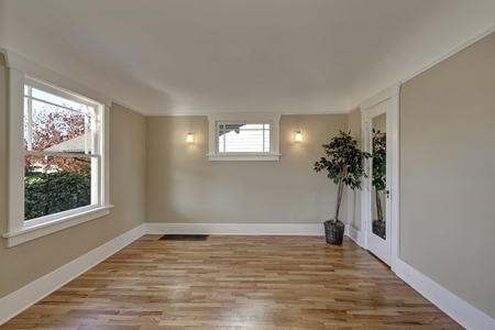 Empty room interior with taupe brown walls, hardwood floor in freshly renovated home.