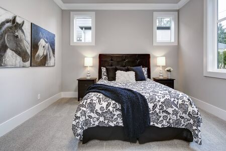 Bedroom interior with painting of horses and black and white bed.