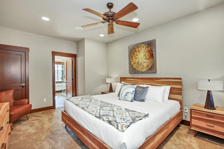 Cozy master bedroom interior features large wood bed with headboard. Northwest, USA
