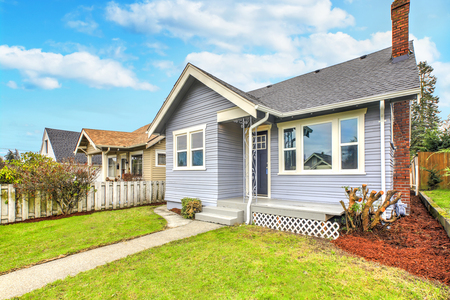 Charming blue home exterior with green grass in front Stockfoto - 110173599