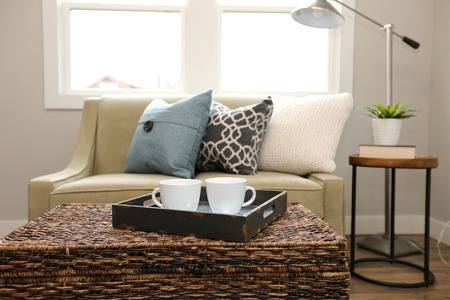 Rattan trunk coffee table with a wood tray and white cups next to a beige sofa with colorful pillows.