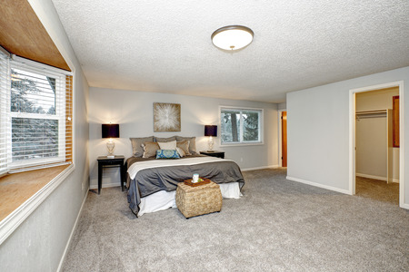 Master bedroom with lots of space, grey carpet floor and rattan trunk Stockfoto