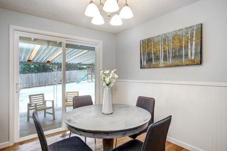 Angolo colazione con tavolo rotondo lavato di bianco e porte in vetro sul patio posteriore. Archivio Fotografico