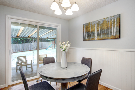 Coin petit-déjeuner avec table ronde blanchie à la chaux et portes vitrées donnant sur le patio arrière. Banque d'images