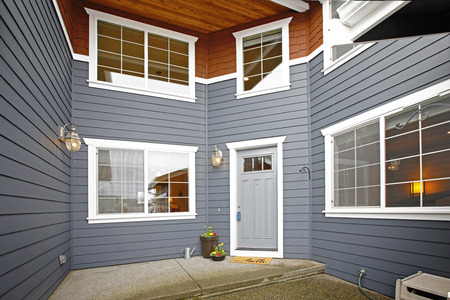 Main entrance of a grey two story tall house exterior.