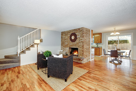 Spacious light filled living room interior accented with brick fireplace and wicker chairs. Zdjęcie Seryjne - 112698370