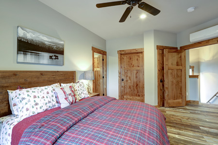 Restful country bedroom furnished with wooden master bed and red bedding Stockfoto - 114013252