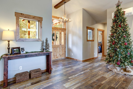 Nice spacious foyer with decorated Christmas tree, rustic wood floor and a console table with baskets.